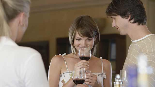 A woman sips a glass of wine while conversing with friends