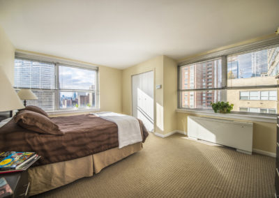 Furnished guest bedroom with natural light at Rittenhouse Claridge apartments