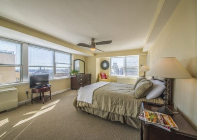 Furnished master bedroom with Philadelphia city views in Rittenhouse Claridge apartment